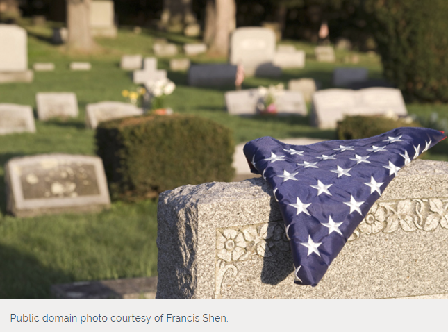 flag draping over tombstone in cemetary